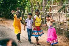 对家庭的印地安小愉快地挥动问候和摆在照相机的女孩和男孩的方式 免版税库存照片