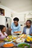 对家庭的愉快的妇女服务食物 免版税库存照片