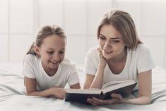 对小女儿的年轻母亲阅读书 库存图片