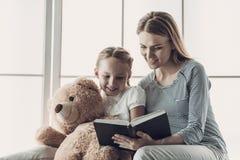 对小女儿的年轻母亲阅读书 图库摄影