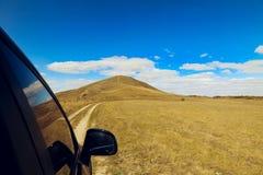 对小山的汽车驱动在蓝天下 免版税图库摄影