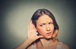 对小心地秘密地听耳朵的姿态的关心的年轻香的妇女手 免版税库存照片
