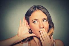 对小心地秘密地听耳朵的姿态的惊奇的年轻香的妇女手 免版税图库摄影