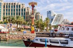 对小游艇船坞的入口,有散步、现代旅馆复合体、棕榈和小船的,埃拉特,以色列 免版税图库摄影