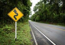 对山的弯曲的路标在乡区 库存图片
