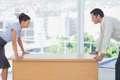 对峙在书桌的商人 免版税库存图片
