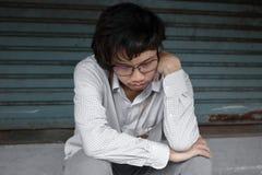 对工作失望或用尽的沮丧的被注重的年轻亚洲商人感觉在外部办公室 图库摄影