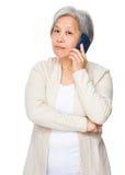 对巧妙的电话的年长妇女谈话 免版税库存图片