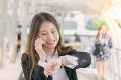 对巧妙的电话andwatching的手表的女商人谈话在步行途中:在概念之外的事务 库存照片