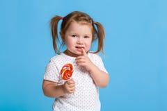 对巨大棒棒糖螺旋糖果微笑负的美丽的矮小的女孩愉快在蓝色背景 库存图片