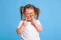 对巨大的棒棒糖螺旋糖果微笑的愉快负的美丽的矮小的女孩被隔绝在蓝色背景 免版税库存图片