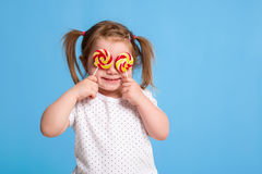 对巨大的棒棒糖螺旋糖果微笑的愉快负的美丽的矮小的女孩被隔绝在蓝色背景 库存照片