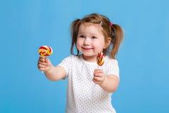对巨大的棒棒糖螺旋糖果微笑的愉快负的美丽的矮小的女孩被隔绝在蓝色背景 库存图片