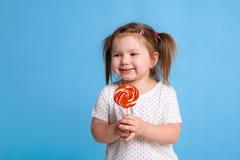 对巨大的棒棒糖螺旋糖果微笑的愉快负的美丽的矮小的女孩被隔绝在蓝色背景 免版税图库摄影