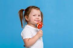 对巨大的棒棒糖螺旋糖果微笑的愉快负的美丽的矮小的女孩被隔绝在蓝色背景 免版税库存照片