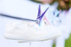 对干净的白色运动鞋在沿其他blured项目的洗衣店干燥绳索垂悬了在后面截去与一个紫色勾子 图库摄影