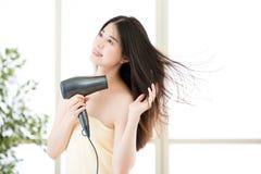 对干毛发的亚洲秀丽妇女吹风器在阵雨以后 免版税库存照片