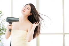 对干毛发的亚洲秀丽妇女吹风器在阵雨以后 库存图片