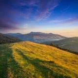 对干草堆和树在山在日落 免版税库存照片