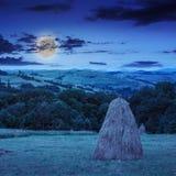 对干草堆和树在山在晚上 库存图片