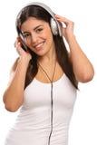 对年轻人的女孩耳机听的音乐 库存图片