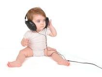 对年轻人的婴孩耳机听的音乐 库存照片