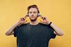 对年轻人的耳机听的人音乐 免版税库存照片