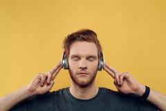 对年轻人的耳机听的人音乐 库存照片