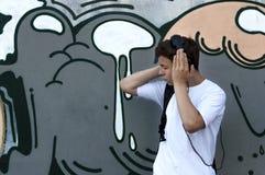 对年轻人的耳机听的人音乐 免版税图库摄影
