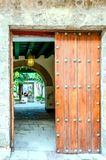 对庭院的古老木门有曲拱的,棕榈树, a 免版税图库摄影
