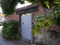 对庭院的木门在有花的古老村庄 库存照片