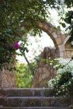 对庭院的石曲拱入口包围与开花的灌木 库存图片