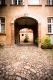 对庭院的被成拱形的入口老欧洲大厦的 库存照片