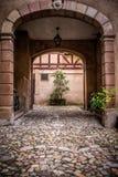 对庭院的被成拱形的入口老欧洲大厦的 免版税库存照片