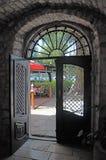 对庭院的被日光照射了古老门道入口 免版税库存照片