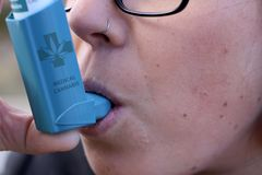 对待哮喘的女孩与大麻吸入器 免版税库存图片