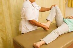 对待四头肌肌肉的生理治疗师 免版税库存照片
