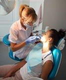 对待在牙齿的美丽的妇女牙医患者的牙  免版税库存图片