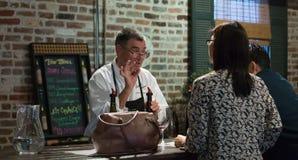 对待夫妇的斟酒服务员与酒 免版税图库摄影