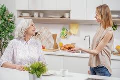 对待她的妈妈的逗人喜爱的女儿与早餐 免版税库存图片