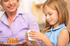 对待孙女的愉快的老婆婆与早餐 库存照片