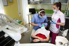 对待患者` s牙的牙医与在牙齿诊所的牙齿工具 牙科 免版税库存照片