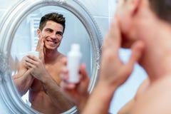 对待sking的健康正面男性与化妆水 免版税库存照片