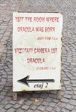 对德雷库拉出生在城堡庭院里在Sighisoara市在罗马尼亚的房子的邀请片剂 图库摄影