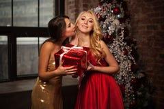 对您的新年快乐庆祝圣诞节的两个美丽的少妇与礼物和kisess 新年` s党 圣诞节 免版税库存照片