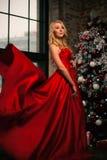 对您的新年快乐红色礼服庆祝圣诞节的美丽的少妇与礼物 新年` s党 圣诞前夕礼品节假日许多装饰品 免版税库存照片