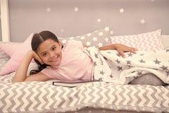 对愉快的末端满意 女孩儿童位置床读了书 孩子准备上床   ?? 库存图片