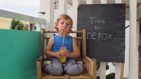 对戒毒所白垩题字的时间 男孩是喝新鲜,健康,由果子做的戒毒所饮料 水果饮料,新鲜的汁液,挤奶 股票视频