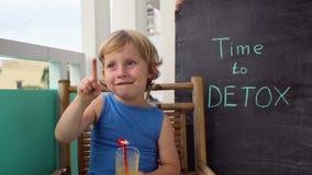 对戒毒所白垩题字的时间 男孩是喝新鲜,健康,由果子做的戒毒所饮料 水果饮料,新鲜的汁液,挤奶 股票录像