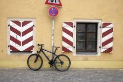 对房子和路标'No停止的墙壁的停放的自行车 图库摄影